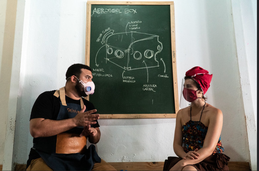 "Picture showing two people sitting on a bench in front of a chalk board that shows a drawing of the ""Aerosol Box"""